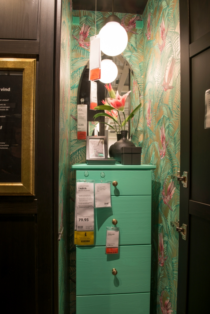 When you open one of the panels... a hidden hallway solution! The colorful wallpaper contrasts with the dark colors in the room.